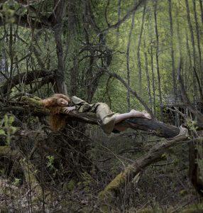 Silentopia. Nainen makaa puun rungolla.